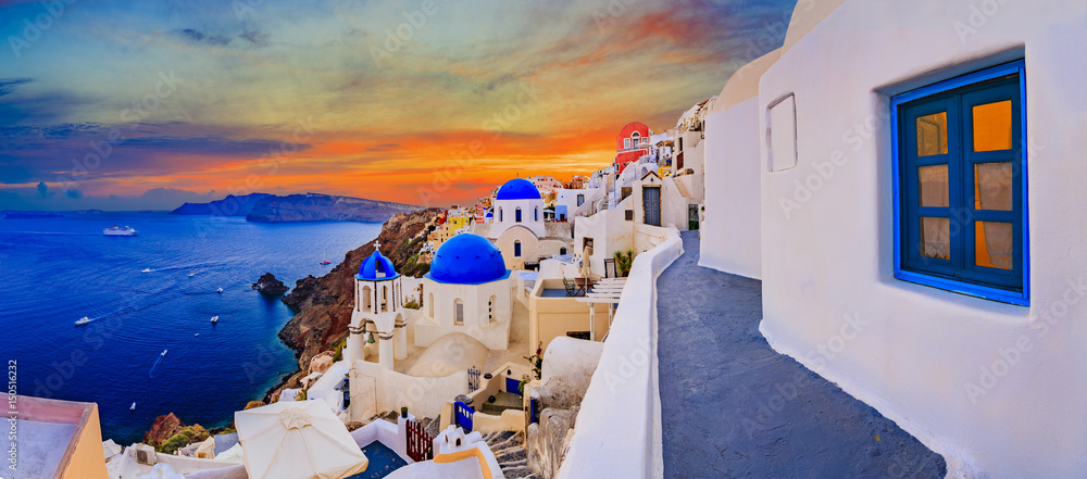 Fototapeta Amazing wide panorama sunset view with white houses on church with blue roofs in Oia village on Santorini island in Greece.