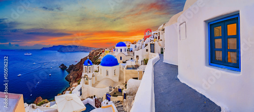 Fototapeta Amazing wide panorama sunset view with white houses on church with blue roofs in Oia village on Santorini island in Greece. obraz
