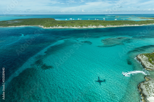 Aerial photo looking down at the airplane's shadow, a jet ski and clear tropical water and islands in the Exuma Chain of islands the Bahamas near Staniel Cay.