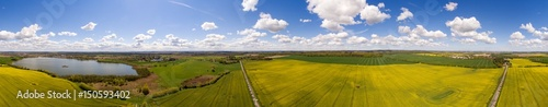 Aerial view 360 degree panorama of colorful raps fields with a lake under blue sky in germany