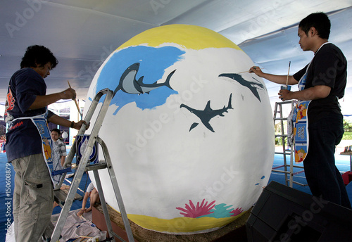Two Indonesian artists paint a giant Easter egg during