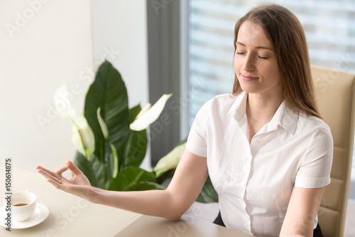 Calm businesswoman meditating in office chair Canvas Print