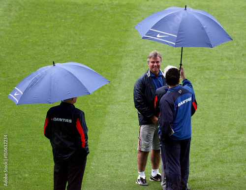 Australian Soccer Coach Guus Hiddink Is Sheltered From The Rain Under An Umbrella During A Training