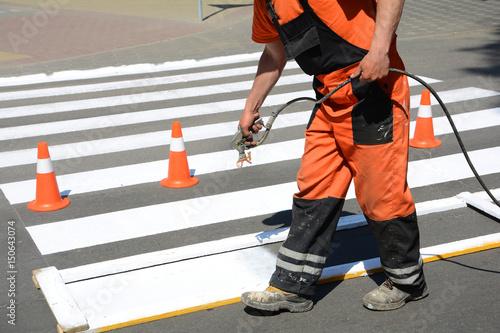 Worker is painting a pedestrian crosswalk  Technical road