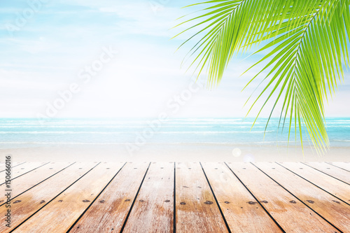 Foto auf Gartenposter Strand Empty wooden table and palm leafs with party on beach background blurred. Concept Summer, Beach, Sea, Relax, Party.