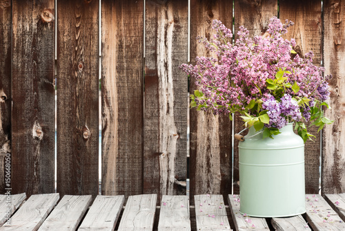 Foto op Canvas Lilac Large bouquet of lilacs in a green container on a rustic wooden table.
