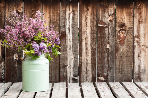 Fotobehang Lilac Large bouquet of lilacs in a green container on a rustic wooden table.