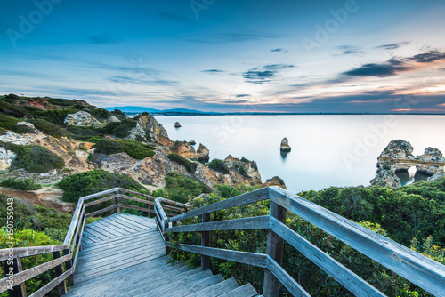 Valokuvatapetti Wooden footbridge walkway to beautiful beach Praia do Camilo on coast of Algarve