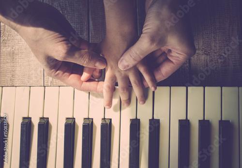 Plakat Matka uczy córkę gry na fortepianie. Koncepcja Dzień Matki. Ręce kobiet i dzieci. Vintage tonowanie. Widok z góry