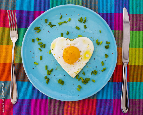 Tasty fried egg in the shape of a heart served on a blue plate.