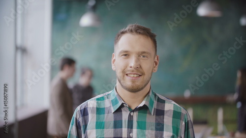 Portrait of young successful businessman at busy office. Handsome male employee looking at camera and smiling.