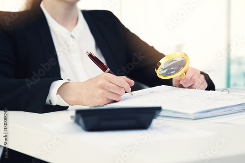 audit concept - auditor with magnifying glass inspecting documents in office Wallpaper Mural