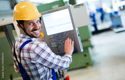 Fotografie, Obraz  Industry Worker entering data in CNC machine at factory