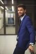 Portrait of handsome businessman standing in corridor