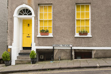 Exterior Of British Traditional House In Queens Parade, Bristol, UK. With Grey Walls, Yellow Front Door And Two Windows With Yellow Curtains. Flowers On The Balcony.