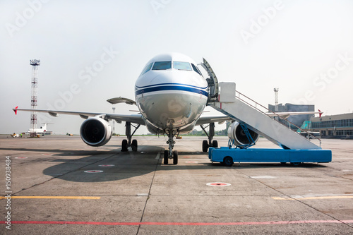 Foto op Aluminium Luchthaven Passenger airplane with open luggage compartment and boarding ramp near at the airport apron