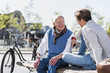 Senior man and adult grandson talking on a bench
