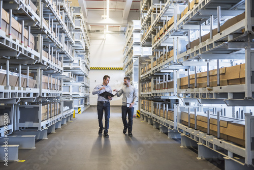 Two men walking in factory warehouse