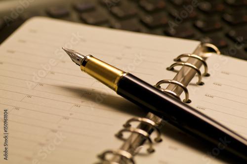 Photo デスクの上に置かれた万年筆と手帳