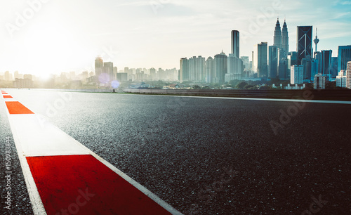 Fototapeta  Racetrack with red and white safety sideline ,modern city background ,dramatic cloudy sky and vintage mood filter apply
