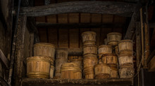 Rows Of Traditional Wooden Stake Barrels With Bamboo Hoops Wait On The Street Behind A Soy Souce Brewing Factory Warehouse In Japan.