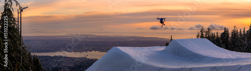 Freestyle skier doing a trick off a jump above city at sunset, Canada, North America