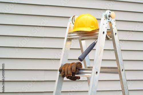 Valokuva  Stepladder, hardhat, gloves and hammer with house siding background