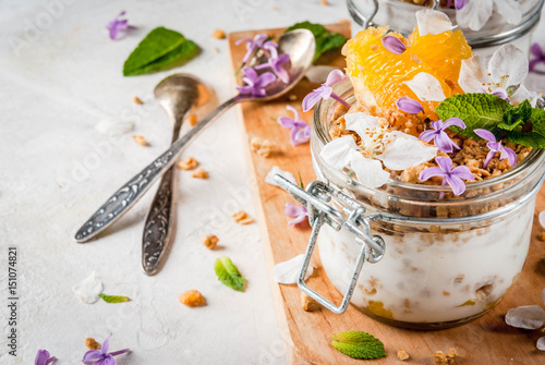 Trendy exotic food. Vegan paleo diet. Breakfast. Yoghurt with granola, fillet slices of orange, mint and edible flowers - lilac, cherry. On a white stone table, with ingredients. Copy space