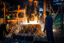 Foundry Worker Pouring Hot Metal Into Cast. Molten Metal. Left Over Material From The Steel Manufacturing Process Is Poured Away On At A Steel Foundry