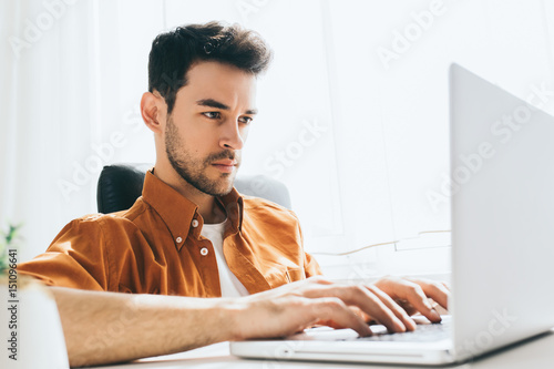 Fotografie, Obraz  Attractive and confident male freelancer sitting in front of the computer with serious and thoughtful expression