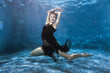 Woman in a dress is dancing under the water in the pool, she is engaged in sports underwater dances.