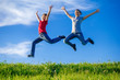 Two kids jumping on green hills against blue sky
