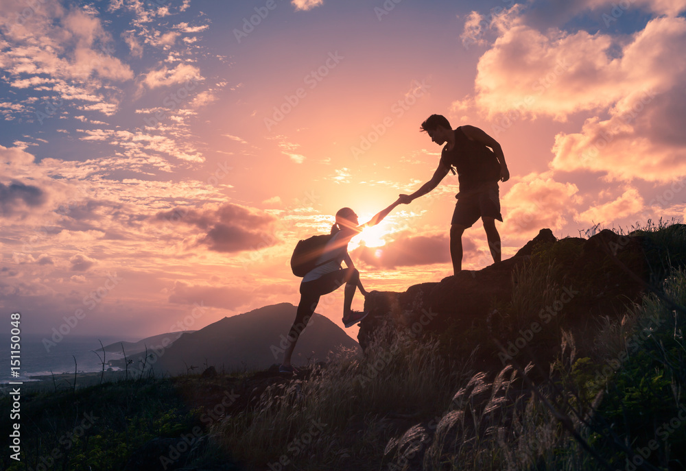 Fototapeta Team work, life goals and self improvement  concept. Man helping his female climbing partner up a steep edge of a mountain.