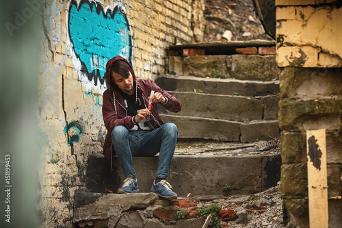 Fototapety, obrazy: Vape man. Photo of a handsome young white guy in the hood vaping an electronic cigarette on an old broken concrete staircase. Lifestyle.