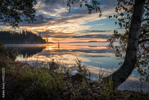 Staande foto Grijze traf. Idyllic landscape with sunset and lake at autumn morning in Finland