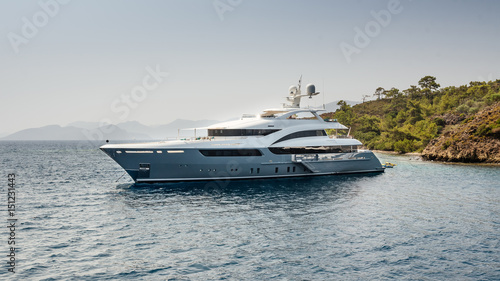 A large private luxurious modern private yacht around the island on a background of the sky