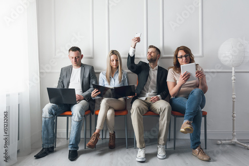 Group of creative people sitting on chairs in waiting room
