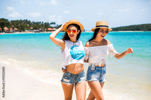 Two cute funny young hipster girls are walking along the beach ... c197ba4bb9f