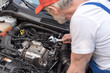 Car mechanic working on car engine