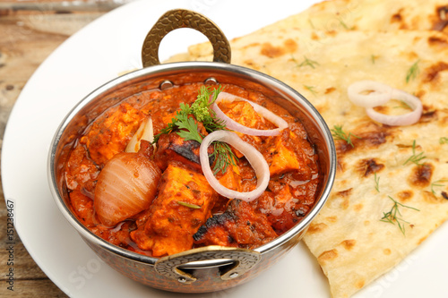 Photo Indian Food or Indian Curry in a copper brass serving bowl with bread or roti