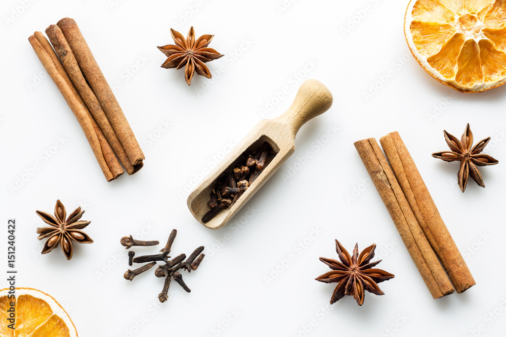 Obraz cloves with wooden scoop and cinnamon on white fototapeta, plakat
