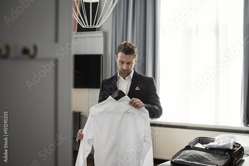 Businessman holding white shirt in coathanger against window at hotel room