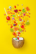 canvas print picture Colorful explosion of candies in coconut on yellow colored background, creative still life, flat lay style