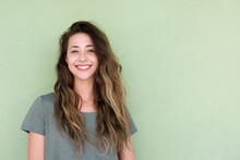 Smiling Young Woman Against Green Background