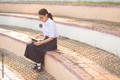 Fototapeta Thai student girl teenager using tablet at the park obraz na płótnie