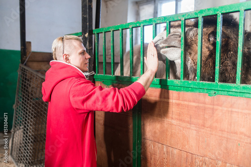 Fotografia, Obraz  The trainer man in the circus stands in front of the cage with a camel