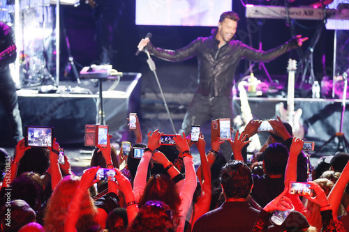 Fans use their mobile devices to take photos and record singer Ricky