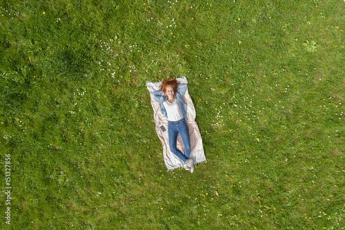 Obraz entspannte frau liegt auf einer grünen wiese und entspannt - fototapety do salonu