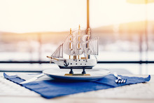 Miniature Sailing Ship Made Of Wood Stands In A Plate In The Restaurant, Behind It There Is A Window On The Sea. Concept Interior Surroundings.