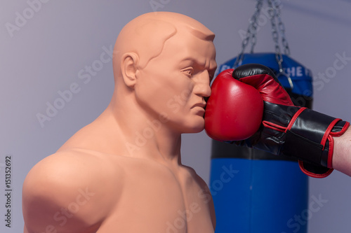 Photo  Red boxing gloves punching a dummy mannequin doll on a gym with a blue punching